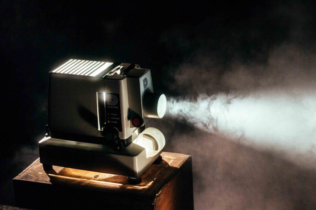 Vanha elokuvaprojektori heijastaa pimeydessä
