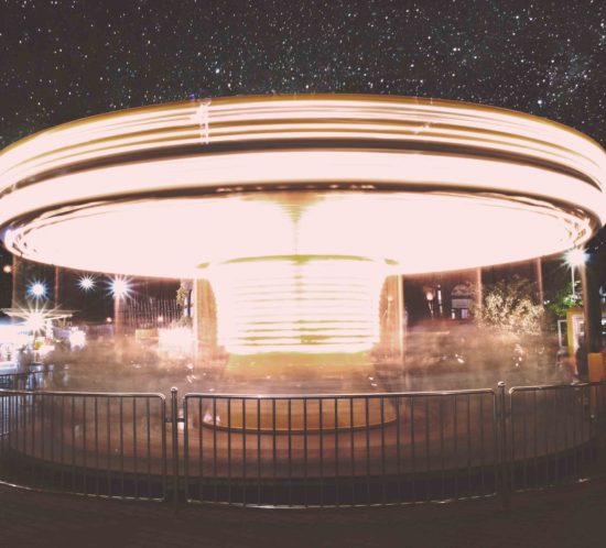 Valaistu karuselli pyörii pimeässä
