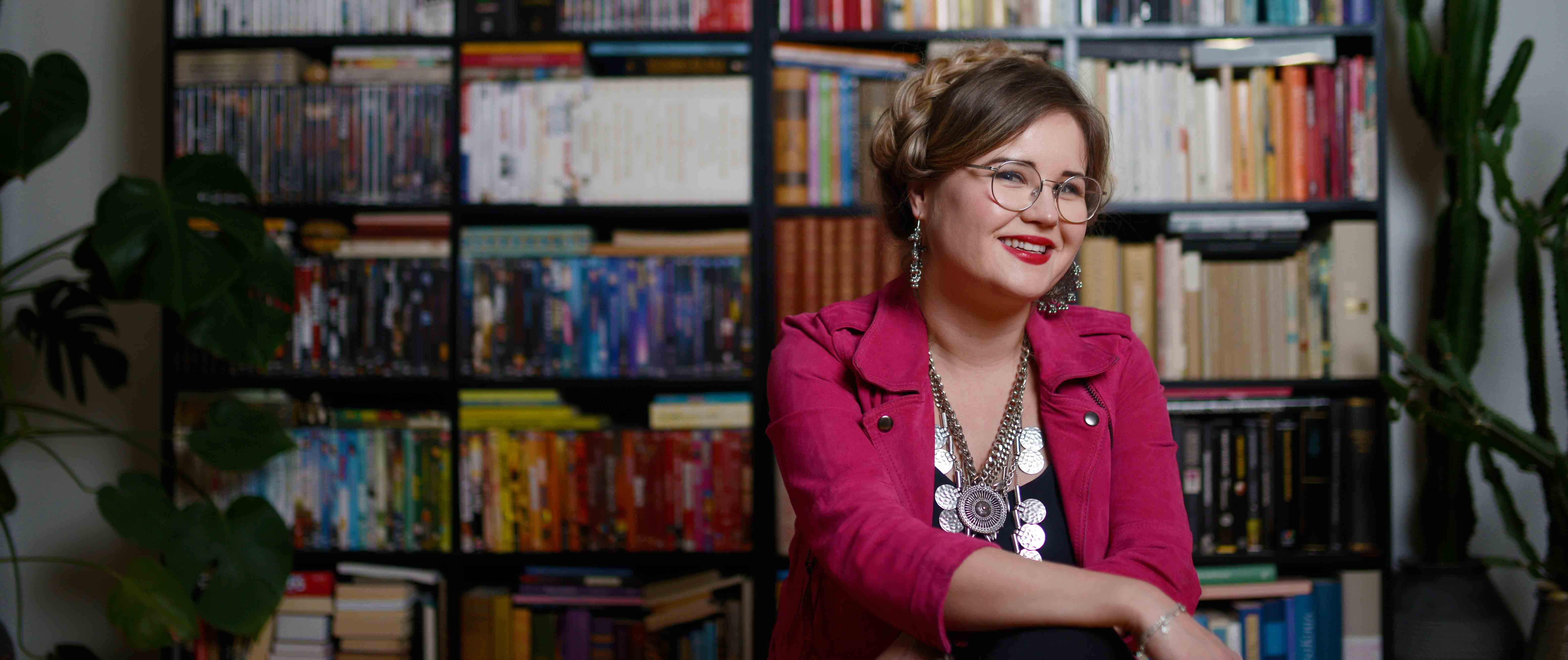 Jenni Hurmerinta kirjahyllynsä edessä